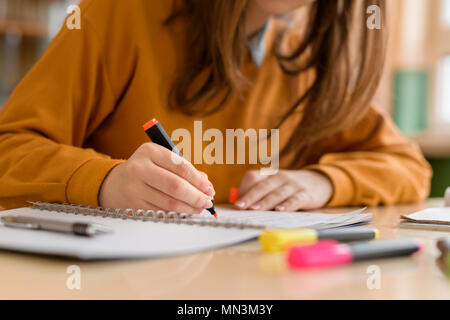 Young unrecognisable female college student in class, taking notes and using highlighter. Focused student in classroom. Authentic Education concept. - Stock Photo