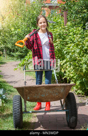 Happy smiling teenage girl working in garden carrying garden tools and pulling big old wheelbarrow - Stock Photo