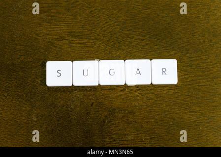 SUGAR word written on plastic keyboard alphabet with dark background - Stock Photo
