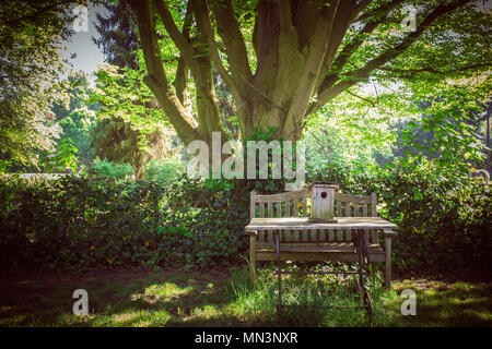 A wooden bench offers a place to sit in a suburban park - Stock Photo