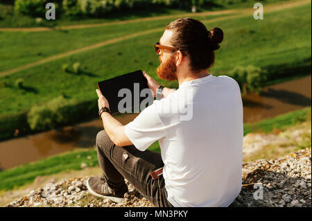 Portrait of young handsome bearded hipster man using a tablet outside. - Stock Photo