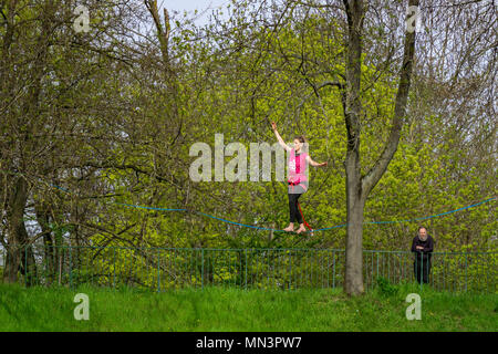 Young female tightrope walker walking on a slackline suspended in the air in a park, Strasbourg, France. - Stock Photo