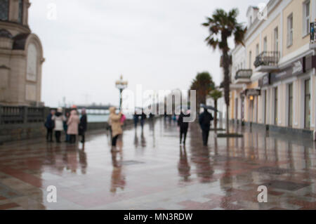 Blurred people walking along the streets on rainy day. - Stock Photo