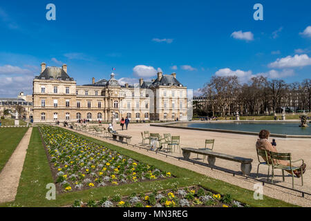 People sitting in the winter sunshine by the octagonal pool of water in the Jardin du Luxembourg ,Paris ,France - Stock Photo