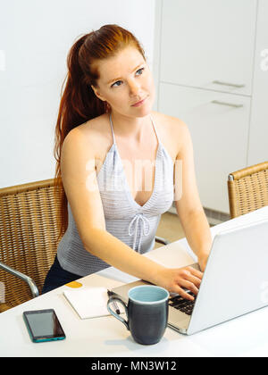 Photo of a beautiful young woman with red hair sitting with a laptop and drinking coffee. - Stock Photo