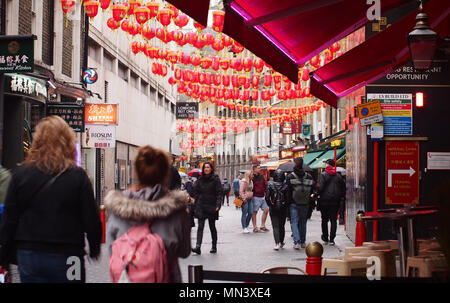 Pedestrians, sightseers and visitors walking under Chinese lanterns in China Town, London - Stock Photo