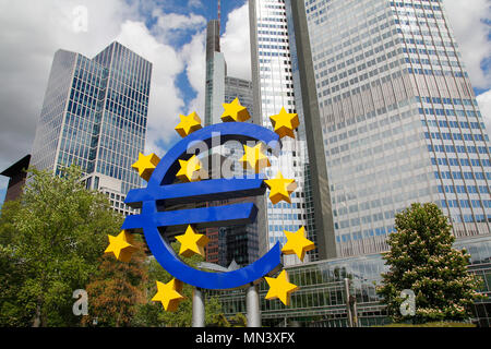 Euro sculpture in the city of Frankfurt, with the Euro Tower in the background - Stock Photo