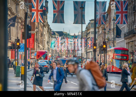 Piccadilly, London, UK. 14 May, 2018. Traffic drives under a canopy of sunlit Union flags installed above Piccadilly to celebrate the forthcoming wedding of HRH Prince Henry of Wales to Ms Meghan Markle on 19 May 2018. Credit: Malcolm Park/Alamy Live News. - Stock Photo