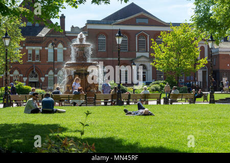 Leicester city May 12th 2018: Visitors basking in the sun around city center water feature. Clifford Norton Alamy Live News. - Stock Photo