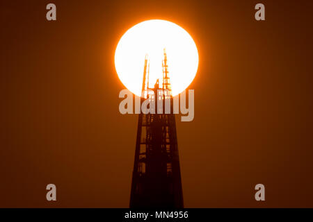 London, UK. 14th May, 2018. UK Weather: The setting sun clips the top of the Shard skyscraper building. © Guy Corbishley/Alamy Live News - Stock Photo