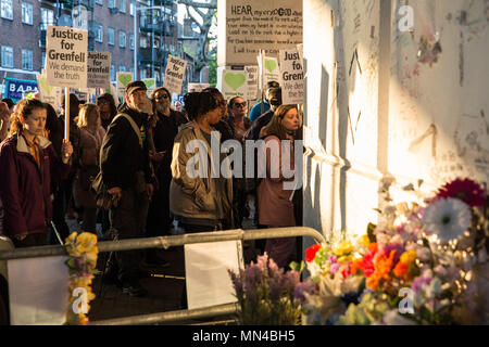 London, UK. 14th May, 2018. Members of the Grenfell community pass a shrine to those who died in the Grenfell Tower fire under the Westway flyover at Latimer Road at the end of the Grenfell Silent March. The march, which takes place on the monthly anniversary of the fire on 14th June 2017, has now returned to the original route starting at the Notting Hill Methodist Church. 71 people died in the Grenfell Tower fire and over 70 were injured. Credit: Mark Kerrison/Alamy Live News - Stock Photo