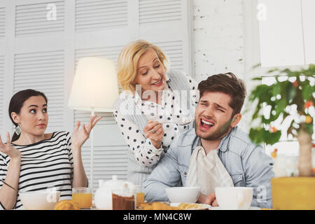 Nice aged woman trying to feed her son - Stock Photo
