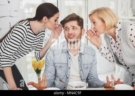 Cheerless young man listening to women