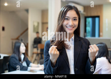 Asian businesswomen Success and winning concept - happy team with raised up hands celebrating the breakthrough and achievements - Stock Photo