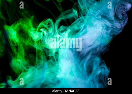 Dense multicolored smoke of   blue and green colors on a white isolated background. Background of smoke vape - Stock Photo