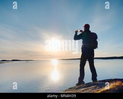 Silhouette of man keep memories with camera phone in his hand. Marvelous sunset at sea, smooth water level - Stock Photo