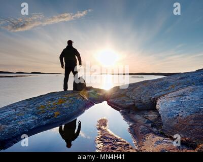 Silhouette of alone man looking toward vibrant sunset. Flare and  reflected in shallow waters of sea level - Stock Photo