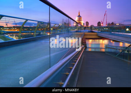Millennium Bridge leading to Saint Paul's Cathedral in central London at sunset - Stock Photo