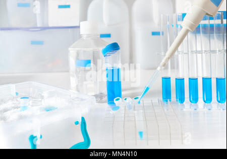 Scientific background in blue and white. Liquid sample loading with automatic pipette, space for your text. This image is toned. - Stock Photo