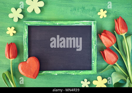 Spring holiday background: blackboard framed with red tulips, wooden heart and flowers on green wood, space for your text - Stock Photo