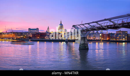 London at sunset, Millennium bridge leading towards illuminated St. Paul cathedral over Thames river with city bathing in electric light. Panoramic to - Stock Photo