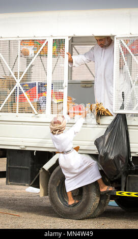 Ibri, Oman, 28th April 2018: young omani boy at a mobile shop trying to reach - Stock Photo