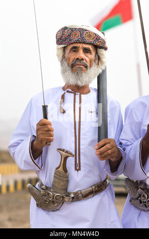 Ibri, Oman, 28th April 2018: omani man with tradiional dagger and a sword, singling tradtitional songs - Stock Photo