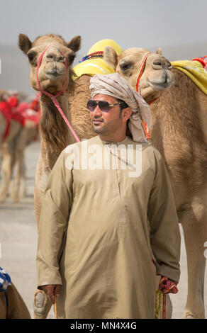 Ibri, Oman, 28th April 2018: omani man with his camel before a race - Stock Photo