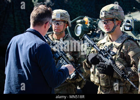 Spc. Michael Hacholski (right), and Pfc. Aidan Flodin (left), infantrymen with the 1st Squadron, 2nd Cavalry Regiment, talk with a student from the Baltic Defense College during an educational visit to Bemowo Piskie Training Area, Poland, May 8, 2018. Battle Group Poland is a unique, multinational coalition of U.S., U.K., Croatian and Romanian Soldiers who serve with the Polish 15th Mechanized Brigade as a deterrence force in support of NATO's Enhanced Forward Presence. (U.S. Army photo by Spc. Hubert D. Delany III /22nd Mobile Public Affairs Detachment) - Stock Photo