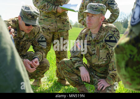 U.S. Army Capt. Kyle Jensen (left) and Chief Warrant Officer 2 Brett Jenkins (right), both UH-60 Blackhawk helicopter pilots with Company B, 3rd Assault Helicopter Battalion, 227th Aviation Regiment, 1st Air Cavalry Brigade, 1st Cavalry Division, discuss flight operations with Estonian soldiers of the 2nd Infantry Brigade, Estonian Defence Force, at a training area just outside of Varstu, Estonia, May 8, 2018. Both countries are strengthening relationships during Operation Hedgehog, a multinational exercise held in Estonia to enhance readiness and interoperability between allies and partners t - Stock Photo