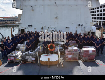 The crew of the Coast Guard Cutter James takes a moment for a group photo before offloading in Port Everglades Thursday, May 10, 2018 approximately 6 tons of cocaine worth an estimated $180 million. The cutter James was involved in six interdictions along with other Coast Guard cutters resulting in the 6 tons of cocaine interdicted at sea in the Eastern Pacific Ocean. U.S. Coast Guard photo by Petty Officer 2nd Class Jonathan Lally - Stock Photo