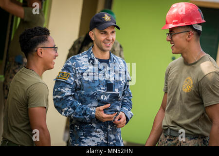 Royal Australian Air Force Flight Lt. Rafael Abboud, center, speaks with U.S. Marine Corps Sgt. Kevin Alberto, left, and Sgt. Andreas Garcia, right, during construction in support of Exercise Balikatan at Calangitan Elementary School in Capas, Tarlac, Philippines. Abboud is a chaplain with 26th Squadron, and is a 36-year-old native of Newcastle, New South Wales, Australia. Alberto and Garcia are combat engineers with 9th Engineer Support Battalion, 3rd Marine Logistics Group, and are 22 and 23-year-old natives of Atlantic City, N.J., and Chicago, Illinois, respectively. Exercise Balikatan, in  - Stock Photo