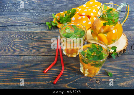 Summer cold drinks. Compote of fruits. Delicious refreshing drink with apricot and mint in glass on a wooden table. - Stock Photo