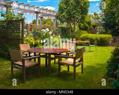 Landscaped Garden with Wooden Dining Table Set in the Shade of Trees - Stock Photo