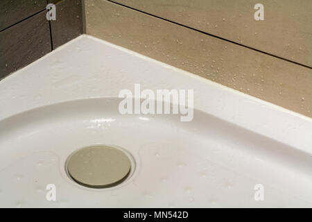 Close-up detail of new modern clean empty white shower cabin with drops of water on nice light beige ceramic tiles on floor and walls. Comfort and hyg - Stock Photo