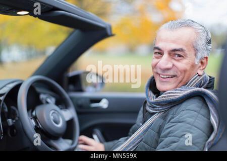 Portrait smiling, confident senior man in convertible - Stock Photo