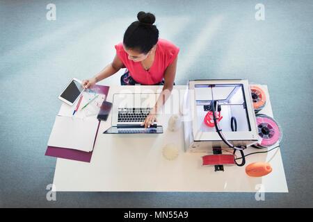 Female designer at laptop next to 3D printer - Stock Photo