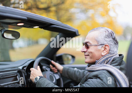 Senior man driving convertible - Stock Photo