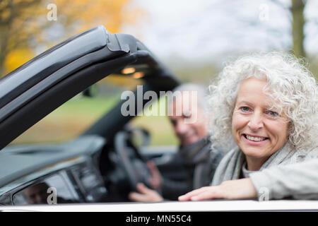 Portrait smiling senior couple in convertible - Stock Photo