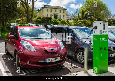 Electric car being charged in a car park in Skibbereen, County Cork, Ireland. - Stock Photo