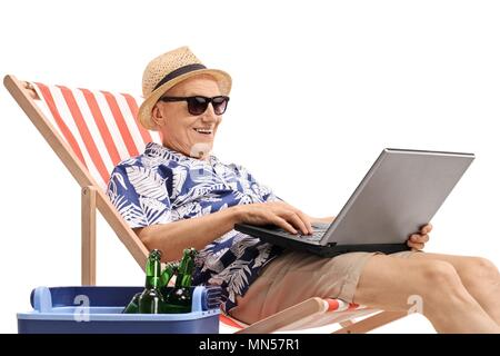 Elderly tourist with a laptop sitting in a deck chair next to a cooling box filled with bottles of beer isolated on white background - Stock Photo