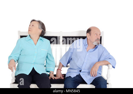 Annoyed eldery couple ignoring each other and sitting back to back on sofa. Having an argument. Isolated white background - Stock Photo