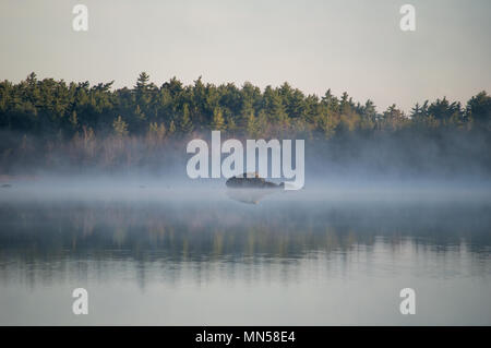 Rock Reflecting in Morning Mist - Stock Photo