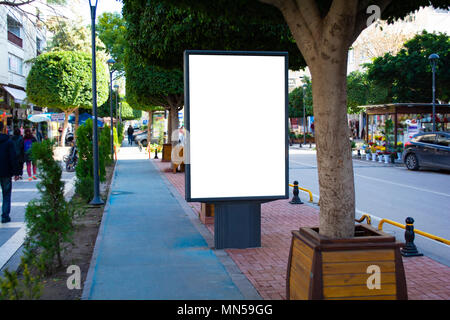 Blank vertical street billboard stand with city background. - Stock Photo