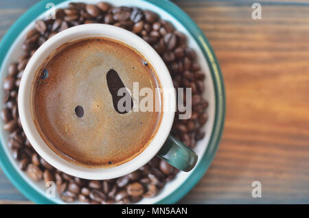 A cup of black coffee on a saucer with coffee beans. - Stock Photo