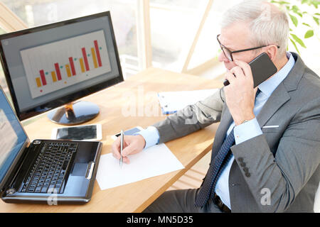 High angle shot of senior investment businessman wearing suit while sitting at office desk in front of laptop and making call. - Stock Photo