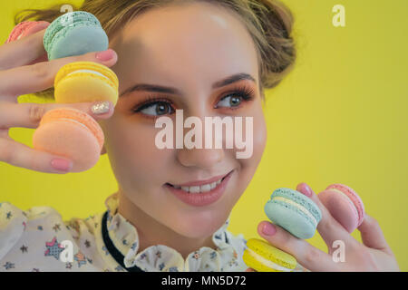 Beautiful professional model with bright makeup holding multicolored macaroon - Stock Photo