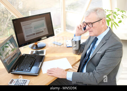 High angle shot of a senior sales man sitting at office desk in front of laptop and talking with somebody in his mobile phone. - Stock Photo