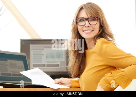 Successful smiling mature businesswoman using laptop and computer while doing some paperwork at the office. - Stock Photo