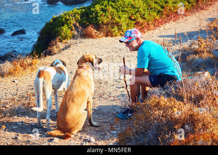 Middle age Caucasian male hiker sitting and resting on a pathway in summertime. Communicating with two dogs in the nature. - Stock Photo
